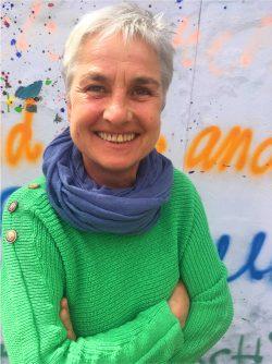 Ines hat einen grünen Pulli und steht vor der Graffitiwand